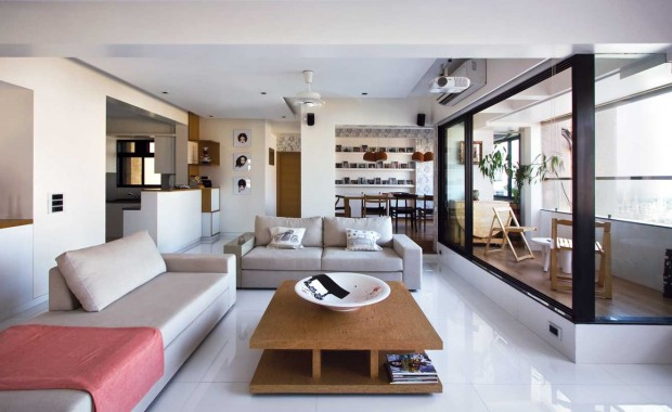 A view of the main living area, which has several charming pockets within a larger space. The sofas and centre table are sourced from Urbanist, New Delhi. To the right, a portion of the living room was carved into a balcony.