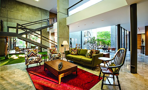 The family area and the staircase block comprise the only double-height volume in this house. The large expanse and the ample view of the greenery create a resort-like vibe.