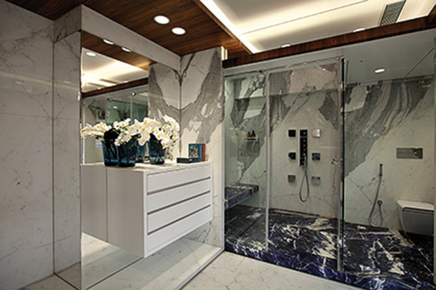 Designed for a contemporary duplex penthouse in Mumbai, this bathroom has been designed in subtle white tones to make the space look larger and clutter-free. Italian statuario marble is used on the floors and walls, with the detailing of blue sodalite marble in the shower and basin area, and the dark veneer on the ceiling and doors to break the monotony. The storage cabinets are finished in lacquer and the basin counter is detailed and appears to be floating. Large peripheral windows provide a panoramic view of the city's skyline and allow natural light to filter into the space thereby enhancing the overall look of the bathroom.