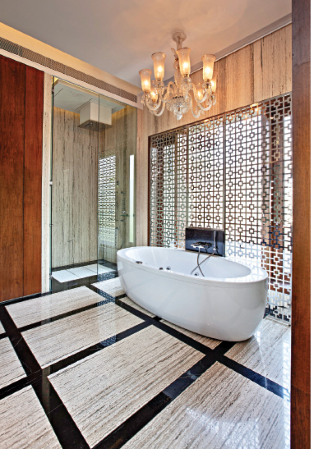 This master bathroom of a luxurious and beautifully-crafted Delhi home flaunts some exquisite materials. The bespoke lacquered black vanity is set against a large mirror which gives the space a grander feel. A free-standing bathtub is set against an intricately carved jaali-patterned screen and is bathed in warm light from the antique chandelier. Italian marble on the floor coupled with the warm wooden panelling make this a glamourous room.