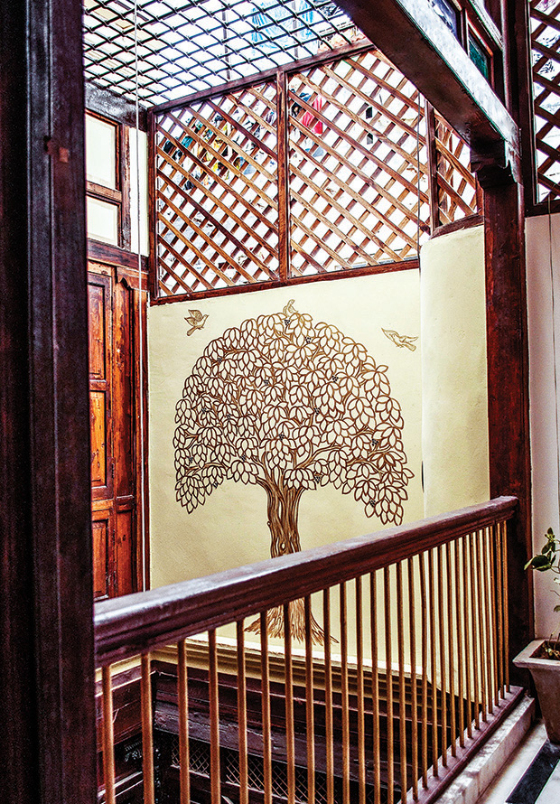 The plain solid mass created by the continuous vertical blank wall of the courtyard is embellished with the traditional Pachhedi painting depicting a tree and birds as viewed from the second floor balcony facing the courtyard.