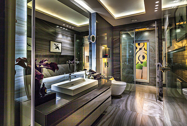 A bachelor's bathroom, this one is sans a conventional door — slip glass (which can become opaque with the slightest touch) is a wall between the bedroom and the bath. A black theme runs through this space with Versace tiles on the floor and wall, with quartz (on the counter top and back of the water closet), to break the monotony.