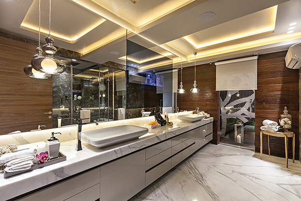 This gorgeous master bathroom for a couple in Gurgaon has the luxury of a calming vertical garden in the courtyard running next to it; and a beautiful lake beyond it. The flooring here is stautario marble with deck flooring in the courtyard and veneer and composite stautario on the counter top. If you note the vanity it would seem almost floating… it is created from marine ply and topped with lacquer. As the couple likes to spend a lot of time in this relaxing bathroom, a mirror television is set next to the large mirror which runs alongside the vanity. The shower area is spacious and sees leather-finished grey marble flooring.