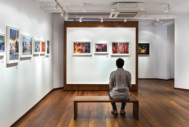 The white canvas on the partition between the reception area and the main gallery, deliberately leaves a border, playing with the notion of furniture being gently placed.