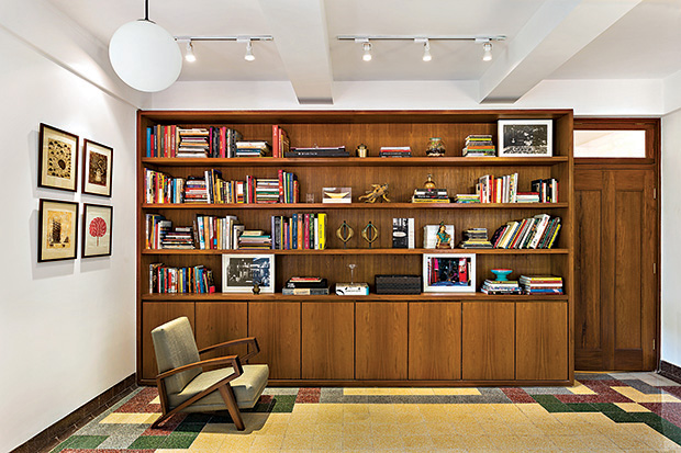 A wall-to-wall library, made using reclaimed Burma teak, is positioned against the wall.